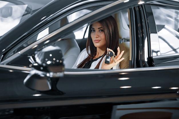La ragazza è seduta in un'auto nuova in concessionaria e mostra le chiavi della macchina.