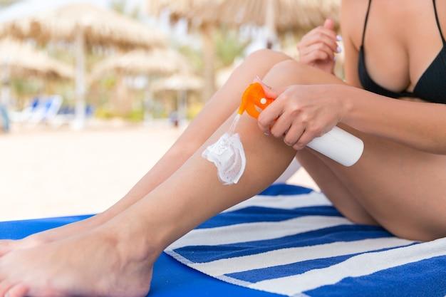 La ragazza è seduta sul lettino e sta applicando la crema solare sulla sua gamba in spiaggia.