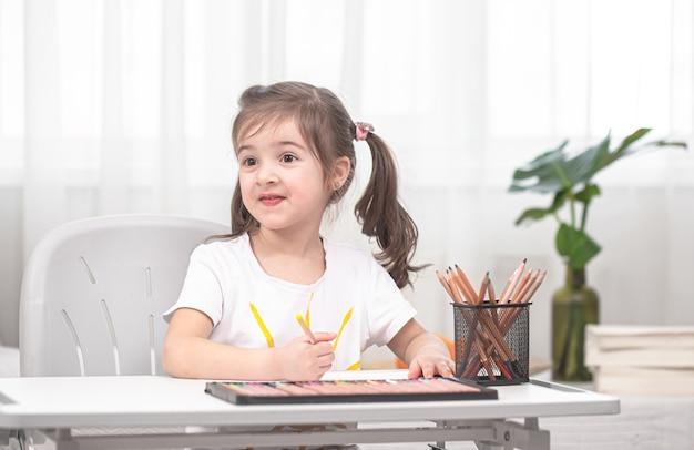La ragazza è seduta al tavolo e fa i compiti. il bambino impara a casa. concetto di istruzione domestica.