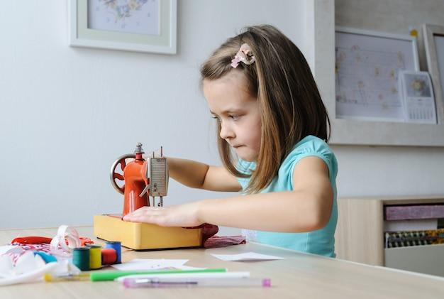 La ragazza è seduta al tavolo e sta cucendo su una macchina da cucire.