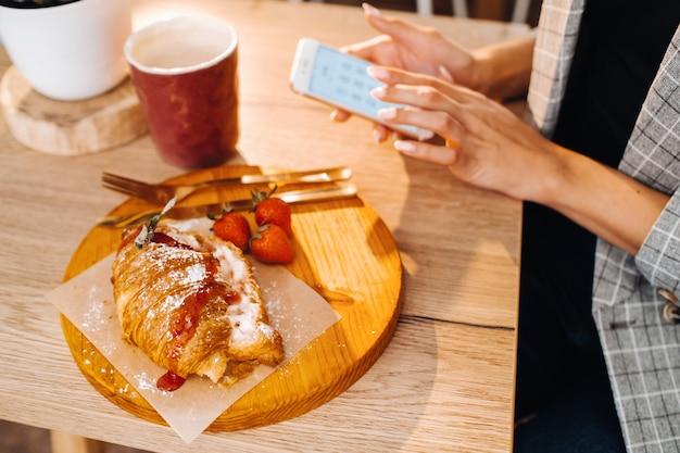 Una ragazza è seduta a un tavolo e invia messaggi di testo sul suo smartphone in un bar. una ragazza è seduta in un bar con un telefono. scrive nel telefono.