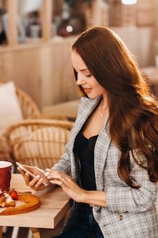 Una ragazza è seduta a un tavolo e scrive messaggi sul suo smartphone in un bar. una ragazza è seduta in un bar con un telefono. scrive nel telefono