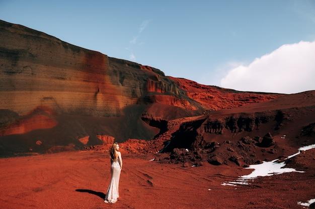 La ragazza è in piedi con la schiena ritratto di un modello di sposa in un abito da sera di nozze d'oro