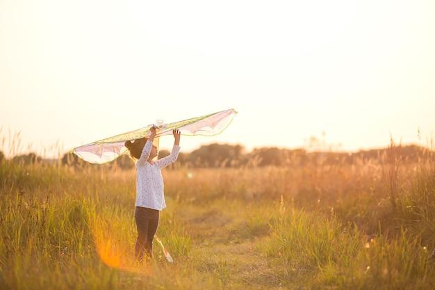 La ragazza è in piedi con le ali in campo, imparando a far volare un aquilone. animazione all'aperto in estate, natura e aria fresca. infanzia, libertà e spensieratezza. i sogni e la speranza dei bambini