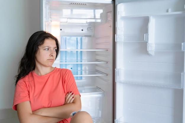 La ragazza è sorpresa dal frigorifero vuoto. mancanza di cibo. consegna del cibo.
