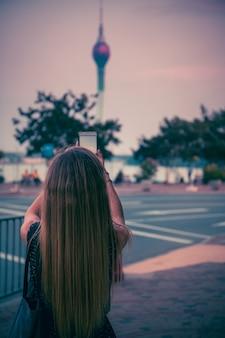 Una ragazza sta fotografando un'alta torre