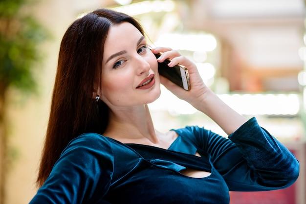 La ragazza sta parlando al telefono al mall.