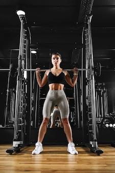 Una ragazza sta allenando le gambe in palestra con uno stile di vita sportivo con bilanciere, mantenersi in forma, motivazione fisica.