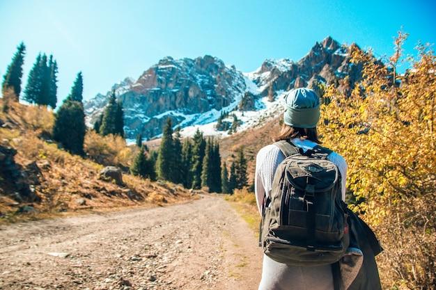 La ragazza sta camminando lungo la strada di montagna. il turista cammina in montagna.