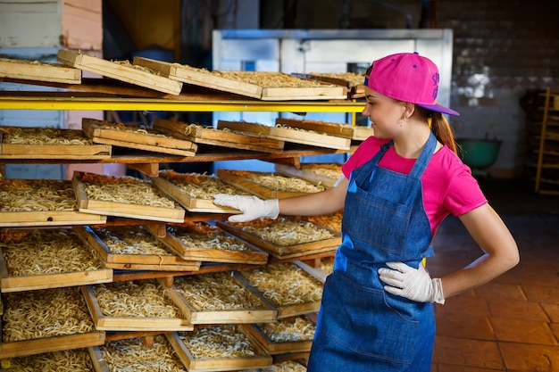 La ragazza sta lavorando alla produzione di spaghetti. fare le tagliatelle. fabbrica di maccheroni.