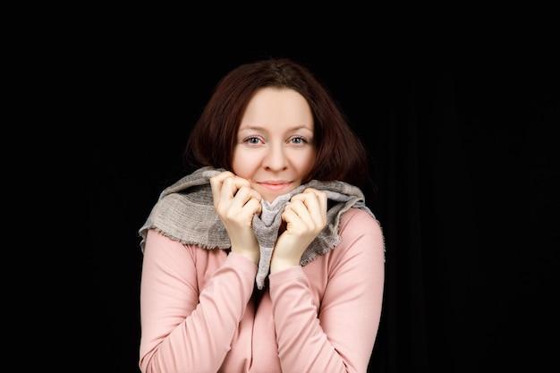 La ragazza è avvolta in una sciarpa grigia. ritratto del primo piano.