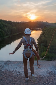La ragazza che salta dal ponte. una ragazza con un tempo incredibile è impegnata nel freestyle nel bungee jumping. una giovane ragazza esegue un trucco inverso nel bungee jumping. salta al tramonto estremamente giovane.