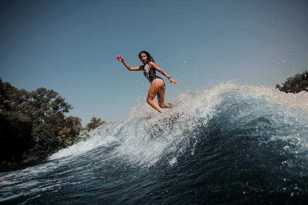 La ragazza che salta sul wakeboard sul lago