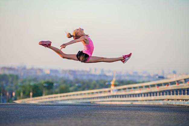 Una ragazza salta nello spago sullo sfondo del cielo serale, sotto c'è un paesaggio urbano.
