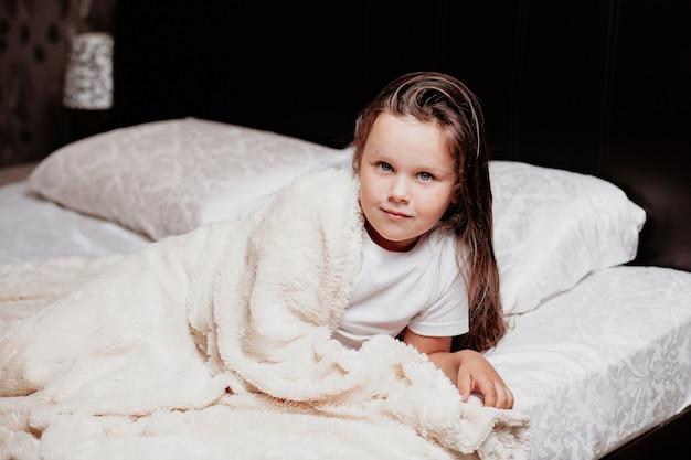 La ragazza si è appena svegliata, fresca bella faccia mattutina di un bambino in camera da letto.