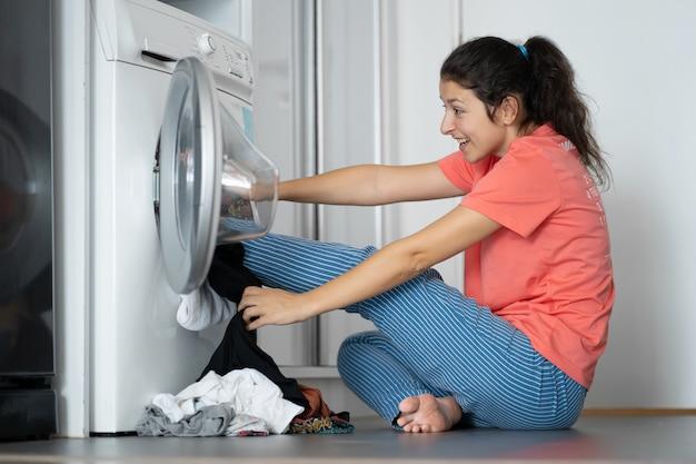 La ragazza dà dei calci alla biancheria sporca nella lavatrice. un sacco di vestiti sporchi che non vanno bene in lavatrice. lavanderia, lavori domestici
