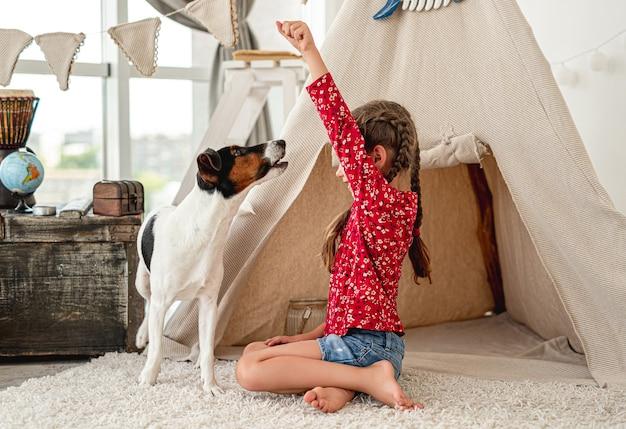 Ragazza bambino che gioca con il cane fox terrier in sala giochi con wigwam