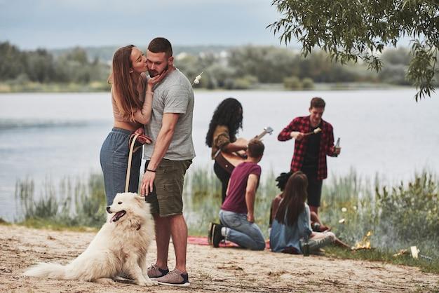La ragazza bacia il suo uomo. un gruppo di persone fa un picnic sulla spiaggia. gli amici si divertono durante il fine settimana.