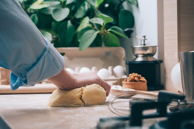 Ragazza che impasta la pasta in cucina, primo piano. una donna a casa prepara l'impasto per deliziosi pasticcini o biscotti. sfondo culinario.