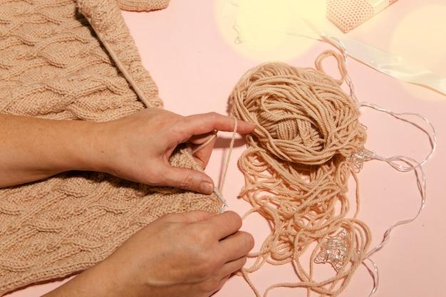 Ragazza che lavora a maglia un maglione caldo vista dall'alto