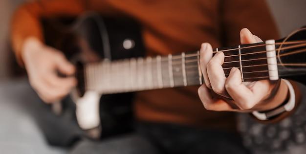 Ragazza che impara a suonare la chitarra con l'aiuto dell'apprendimento online a casa