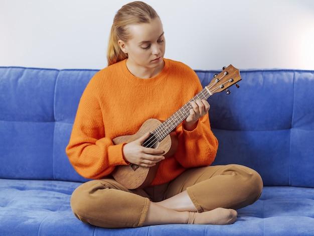La ragazza impara a suonare l'ukulele a casa Foto Premium