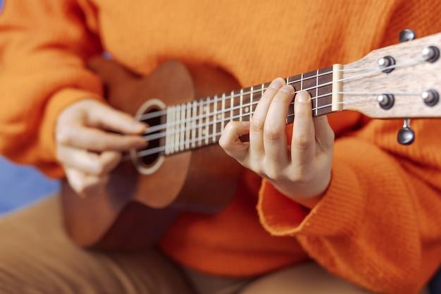 La ragazza impara a suonare l'ukulele a casa