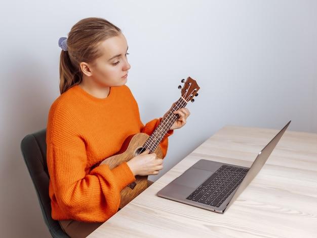 Una ragazza impara a suonare l'ukulele su un laptop