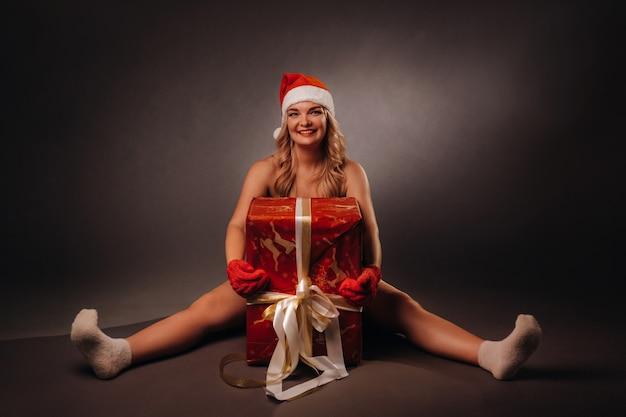 Una ragazza con una giacca di pelle, gambe nude e un cappello di natale si siede su un regalo di natale su uno sfondo nero.