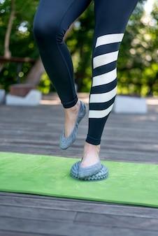 La gamba della ragazza sta con un piede sul disco di bilanciamento con punte. impatto sui punti attivi del piede. cornice verticale