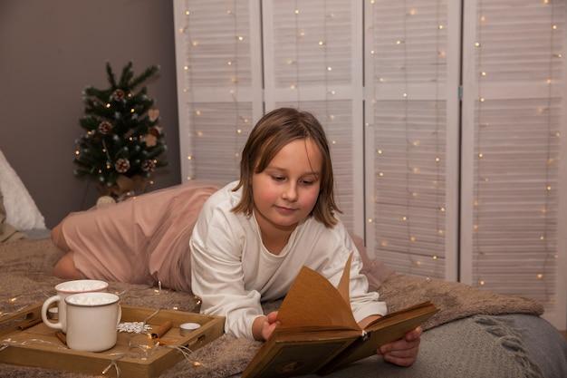 Una ragazza giace su un letto con un libro