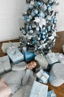 La ragazza si trova sul pavimento, circondata da regali, vicino all'albero di capodanno, vista dall'alto, concetto di capodanno