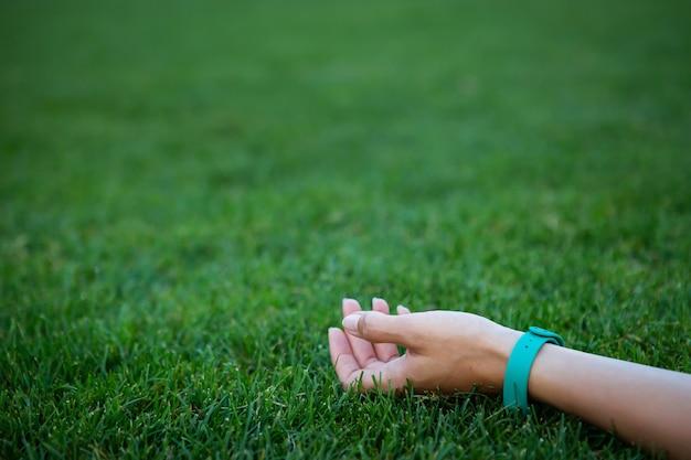 La ragazza si trova sull'erba, la sua mano è su un prato verde liscio appena falciato, si rilassa all'aria aperta. sfondo, posto per un'iscrizione.