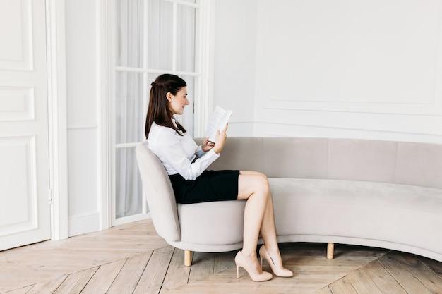 Una ragazza in abiti leggeri è seduta sul divano e legge un libro