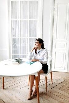 Ragazza in abiti leggeri, seduta su una sedia in una stanza