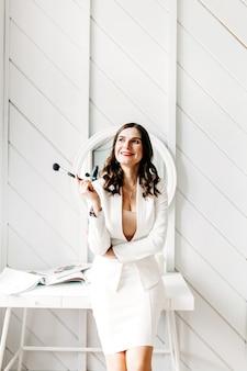 Una ragazza in un abito leggero con i capelli scuri si trova davanti allo specchio e applica il trucco