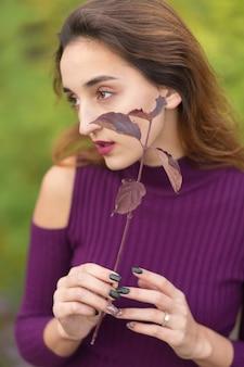Ragazza in abito lilla sulla natura in autunno, ritratto di una bella ragazza in autunno nella foresta