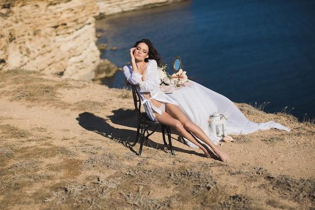 Ragazza in lingerie in cima a una montagna con vista sull'oceano. accuse della sposa, mattina della sposa.