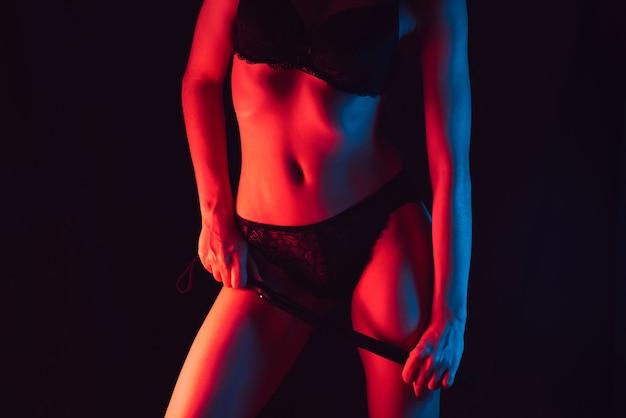 Ragazza in lingerie con bella figura snella con frusta di cuoio in mano per giochi erotici bdsm