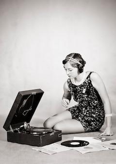 Ragazza che ascolta i dischi del grammofono. vintage ▾