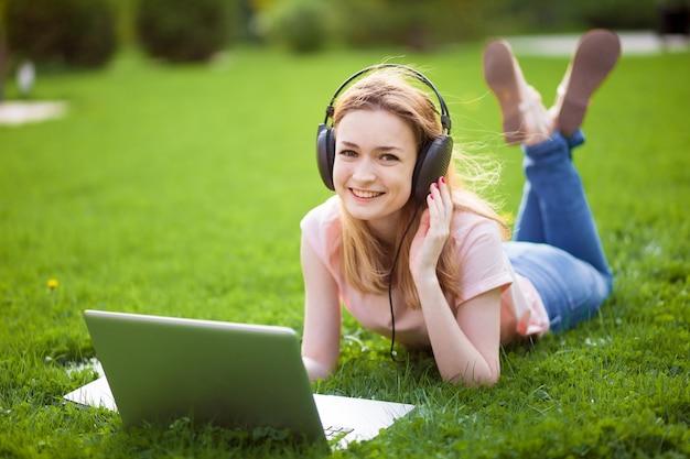Ragazza che ascolta la musica da un computer portatile nel parco