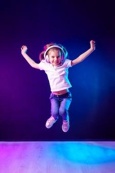 Ragazza che ascolta la musica in cuffie sulla parete variopinta scura. ragazza danzante. piccola ragazza felice che balla alla musica. bambino sveglio che gode della musica da ballo felice.