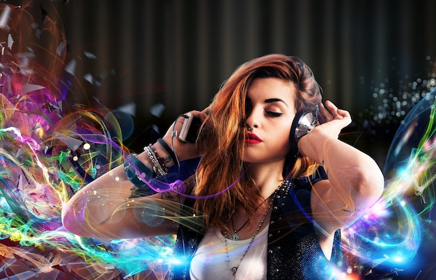 Ragazza che ascolta la musica con le cuffie su striature colorate luminose