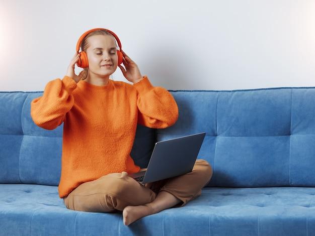 La ragazza ascolta musica in cuffia al computer