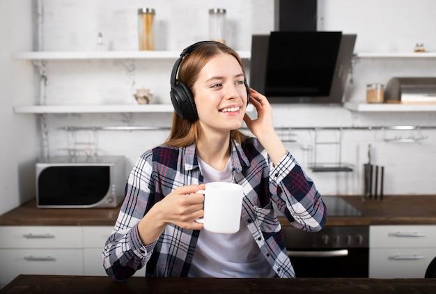 La ragazza ascolta musica in cuffia e beve caffè