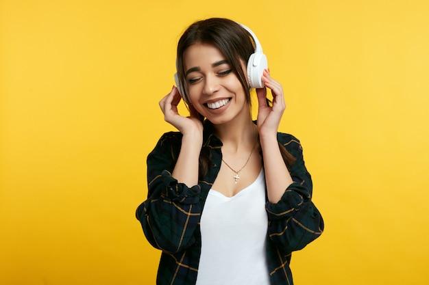 La ragazza ascolta musica e tiene le mani sulle cuffie chiude gli occhi dal piacere