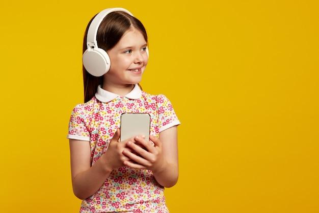 La ragazza ascolta musica in cuffie bianche usa il telefono cellulare per chattare
