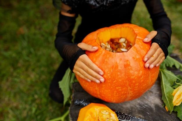 Ragazza, bambino mani tenere la zucca prima di intagliare per halloween, prepara jack o'lantern. decorazione per la festa, piccolo aiutante di famiglia, vista dall'alto, primo piano, vista dall'alto, spazio copia
