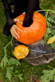 Ragazza, mani di bambino che estrae semi e materiale fibroso da una zucca prima di scolpire per halloween, prepara jack o'lantern. piccolo aiutante di famiglia, vista dall'alto, vista dall'alto, spazio copia
