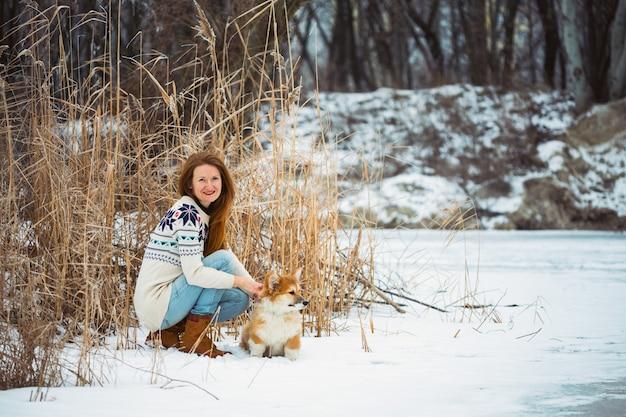Ragazza e piccolo cucciolo lanuginoso corgi carino all'aperto. inverno